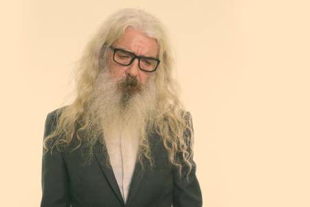 Studio shot of sad senior bearded businessman wearing eyeglasses and looking down