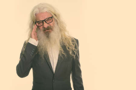 Studio shot of stressed senior bearded businessman wearing eyeglasses while having headache