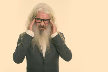 Studio shot of stressed senior bearded businessman wearing eyeglasses while having headache with both hands on head 版權商用圖片