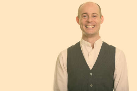 Happy bald Caucasian man smiling and wearing vest
