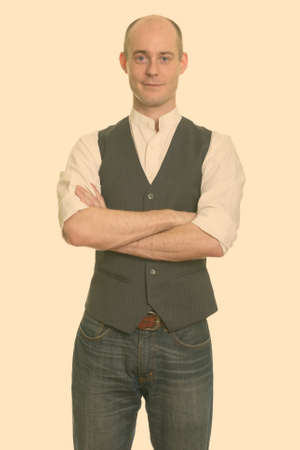 Bald Caucasian man wearing vest with arms crossed