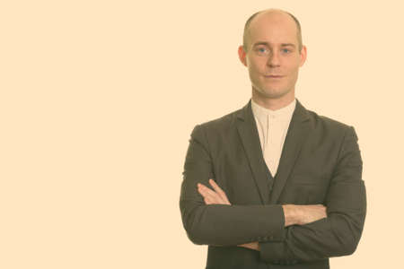 Portrait of handsome bald businessman in suit with arms crossed