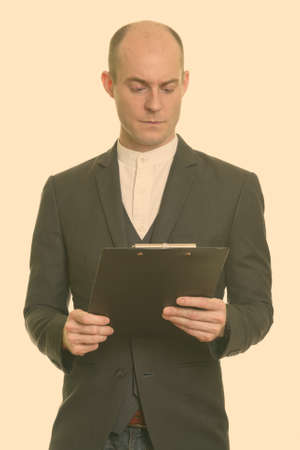 Close up of bald Caucasian businessman reading on clipboard 版權商用圖片