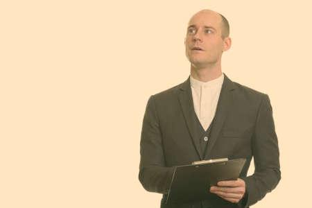 Bald Caucasian businessman holding clipboard while thinking 版權商用圖片