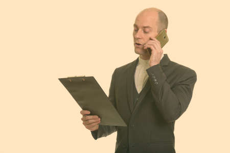 Bald Caucasian businessman reading on clipboard while talking on mobile phone