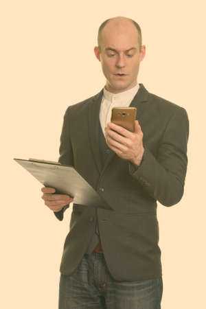Bald Caucasian businessman holding clipboard while using mobile phone