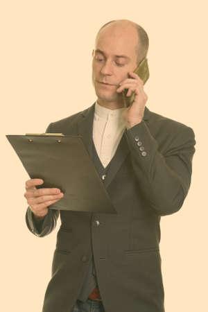Bald Caucasian businessman talking on mobile phone while reading on clipboard 版權商用圖片