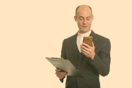 Happy bald Caucasian businessman smiling and holding clipboard while using mobile phone 版權商用圖片