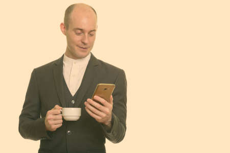 Happy bald Caucasian businessman smiling while holding mobile phone and coffee cup 版權商用圖片