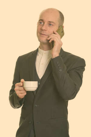 Thoughtful happy bald Caucasian businessman smiling and talking on mobile phone while holding coffee cup