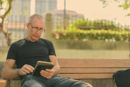 Bald senior tourist man using digital tablet while wearing eyeglasses and sitting on the wooden bench at peaceful park Banque d'images