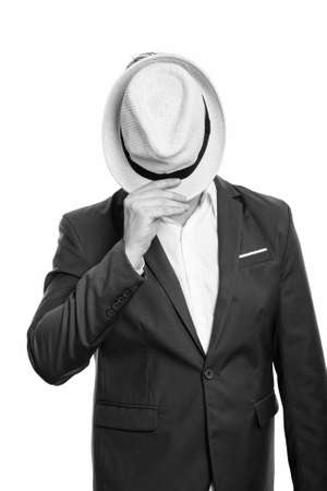 Studio shot of mature businessman covering face with hat Standard-Bild