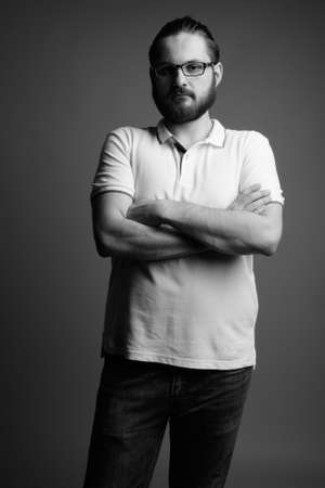 Young bearded man wearing white polo shirt against gray background