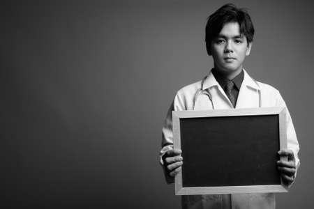 Young handsome Asian man doctor against gray background Stock Photo