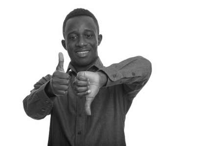 Young happy African man smiling while giving thumbs up and down