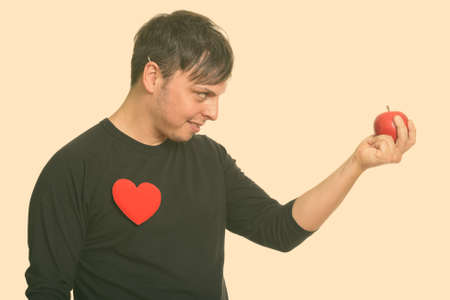 Profile view of crazy Caucasian man holding red apple ready for Valentines day