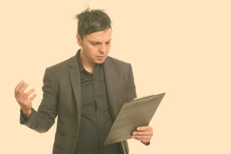 Studio shot of angry Caucasian businessman reading clipboard