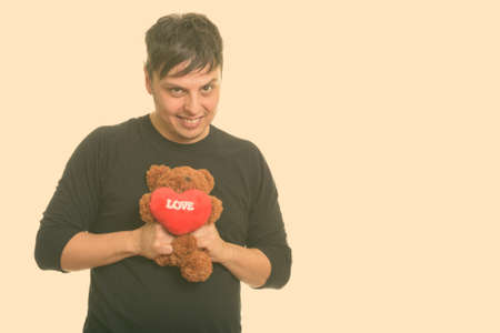 Studio shot of crazy man squeezing teddy bear for Valentines day