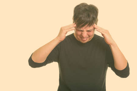 Studio shot of Caucasian man having headache
