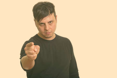 Studio shot of angry man pointing finger at camera 版權商用圖片