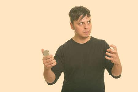 Studio shot of angry man holding mobile phone while thinking 版權商用圖片
