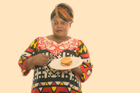 Studio shot of fat black African woman holding and pointing at burger served on white plate Stock fotó