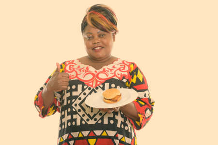 Studio shot of happy fat black African woman smiling and giving thumb up while holding burger served on white plate Stock fotó