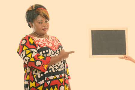 Studio shot of fat black African woman pointing at blank blackboard Stock fotó