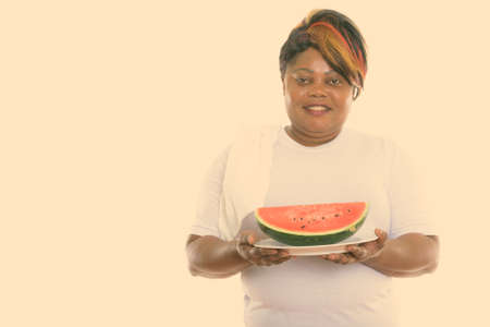 Studio shot of happy fat black African woman smiling while holding slice of watermelon served on white plate ready for gym Stock fotó