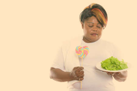 Studio shot of fat black African woman looking lettuce served on white plate and holding heart shaped lollipop