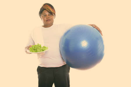 Studio shot of fat black African woman thinking while holding exercise ball and lettuce served on white plate ready for gym
