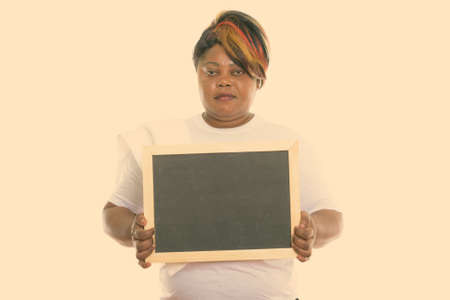 Studio shot of fat black African woman holding blank blackboard ready for gym Stock fotó