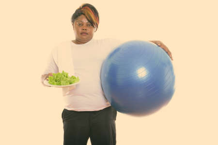 Studio shot of fat black African woman holding exercise ball and lettuce served on white plate ready for gym