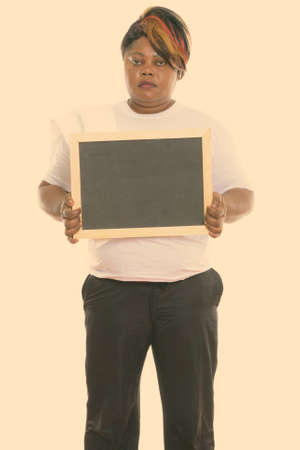 Studio shot of fat black African woman standing while holding blank blackboard ready for gym