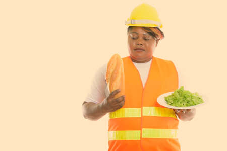 Studio shot of fat black African woman construction worker looking at bread and holding lettuce served on white plate Stock fotó