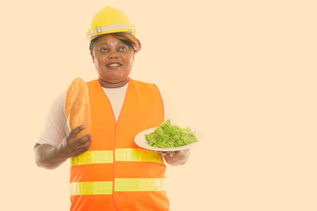 Thoughtful happy fat black African woman construction worker smiling while holding bread and lettuce served on white plate