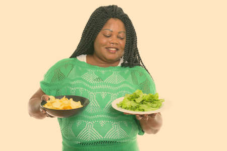 Studio shot of happy fat black African woman smiling while holding bowl of potato chips and looking at lettuce served on white plate Stock fotó
