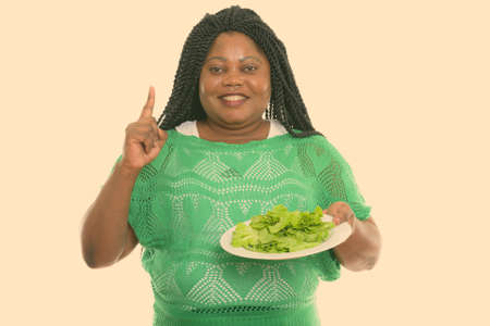 Studio shot of happy fat black African woman smiling while holding lettuce served on white plate and pointing finger up