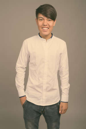 Young Asian teenage boy against gray background