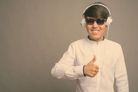 Young Asian teenage boy listening to music against gray background