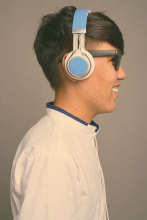 Young Asian teenage boy listening to music against gray background Stock fotó