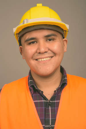 Young Asian man construction worker against gray background Imagens