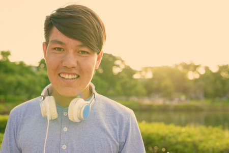 Young Asian teenage boy wearing headphones while relaxing at the park