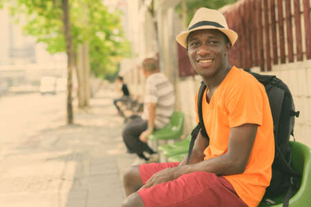 Young happy black African tourist man smiling and thinking while sitting at the bus stop in the streets of Bangkok Thailand