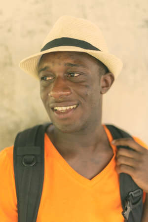 Face of young happy black African tourist man smiling and thinking against concrete wall in the sky train station of Bangkok Thailand Reklamní fotografie
