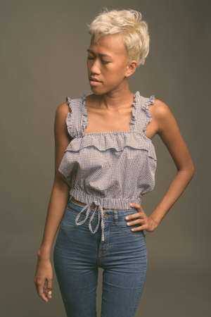 Young beautiful rebellious woman with short hair against gray background
