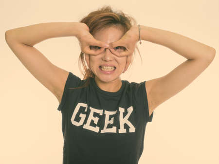 Studio shot of young Asian geek girl making hand mask gesture against white background