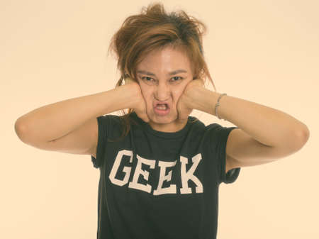 Studio shot of young Asian geek girl squeezing her face against white background