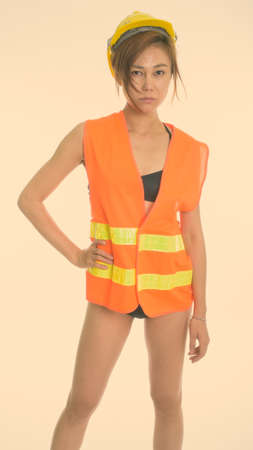 Studio shot of young Asian woman construction worker standing and posing while wearing underwear against white background