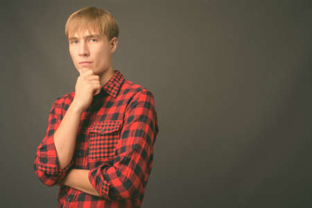 Young handsome man with blond hair against gray background